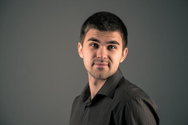 Sorridente giovane uomo bello tifo contro un muro scuro