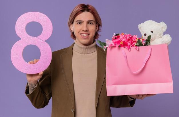 Sorridente giovane bell'uomo con numero rosa otto e sacchetto regalo con fiori e orsacchiotto