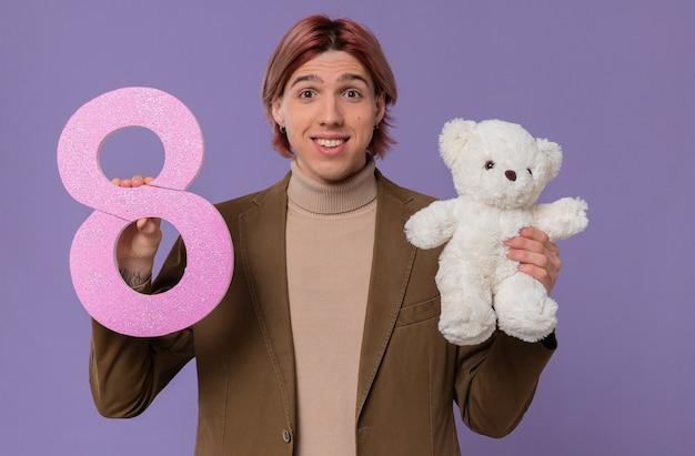 Sorridente giovane bell'uomo che tiene il numero rosa otto e un orsacchiotto bianco