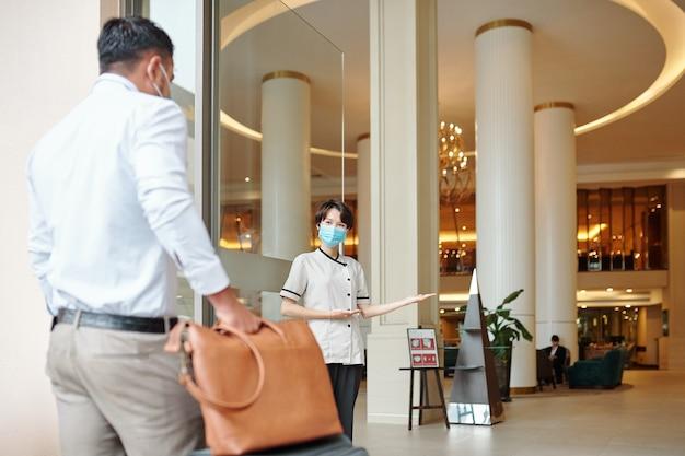 Sorridente giovane portiere dell'hotel che fa un gesto di benvenuto e invita gli ospiti all'interno