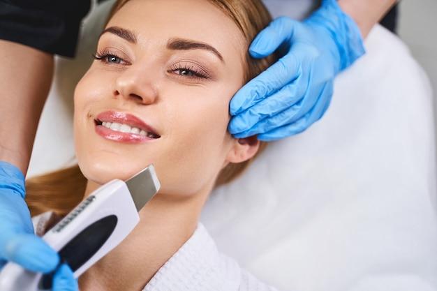 La giovane donna sorridente sta venendo dal cosmetologo per ottenere la pulizia del viso ad ultrasuoni nel salone di bellezza