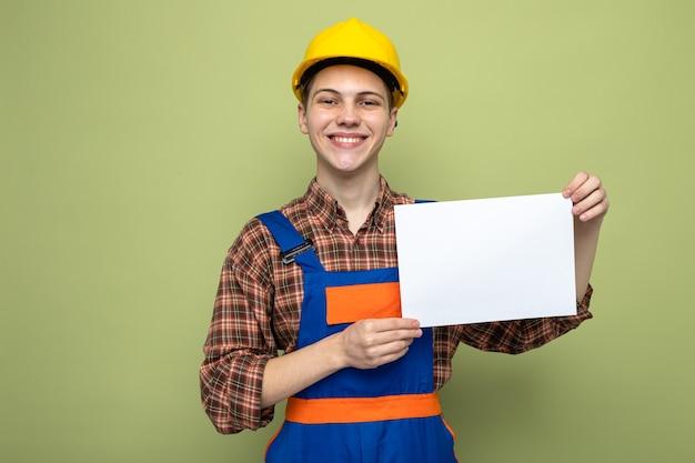 Sorridente giovane costruttore maschio tenendo la carta indossando l'uniforme