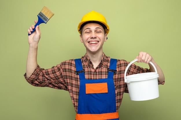 Sorridente giovane costruttore maschio che indossa l'uniforme che tiene il secchio con il pennello