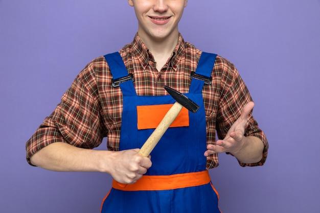 Sorridente giovane costruttore maschio indossando uniforme tenendo martello