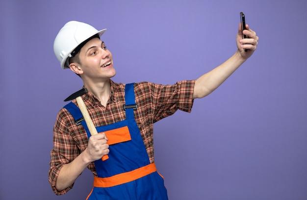 Il giovane costruttore maschio sorridente che indossa l'uniforme con il martello prende un selfie