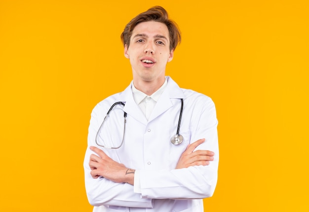Sorridente giovane medico maschio indossando veste medica con lo stetoscopio che si incrociano le mani