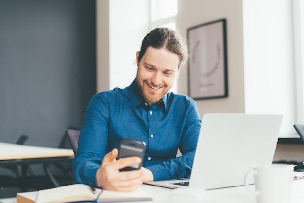 Sorridente giovane impiegato di sesso maschile che utilizza lo smartphone mentre si lavora al computer portatile in un moderno centro ufficio