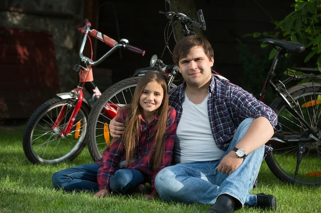 Giovane sorridente e ragazza carina che si rilassano sull'erba al parco dopo aver guidato le biciclette