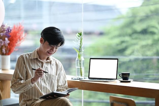 Sorridente giovane imprenditore seduto in ufficio luminoso e prendere appunti sul taccuino.