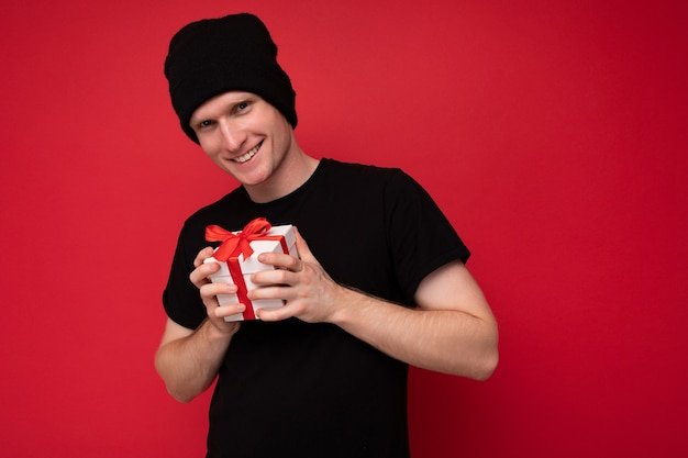 Sorridente giovane uomo isolato su sfondo rosso muro che indossa un cappello nero e maglietta nera azienda confezione regalo bianca con nastro rosso e guardando la fotocamera.