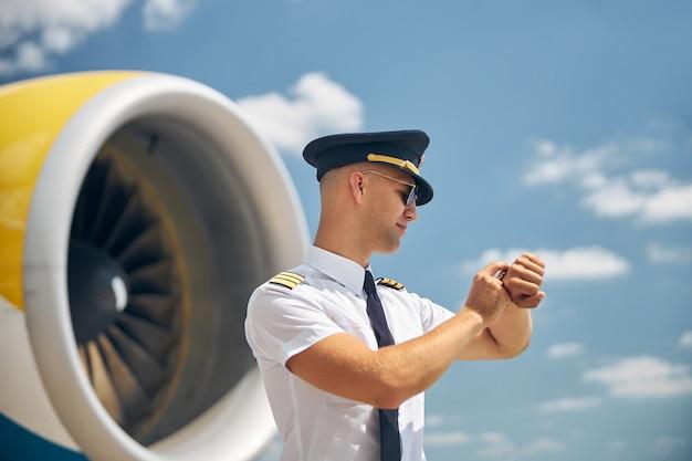 Giovane sorridente con cappello da pilota e occhiali da sole che controlla il tempo mentre aspetta il suo volo all'aeroporto con aereo e cielo blu su sfondo sfocato