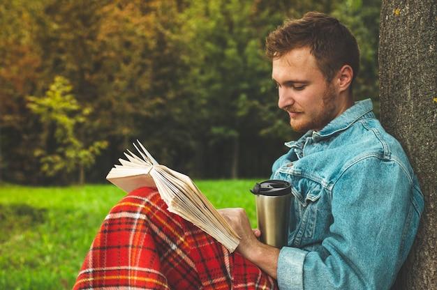 Libro di lettura sorridente del giovane all'aperto con un plaid rosso caldo e una tazza di tè. vacanze autunnali e concetto di stile di vita.