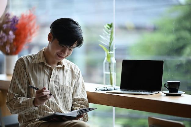 Sorridente giovane uomo seduto in ufficio luminoso e prendere nota sul taccuino.