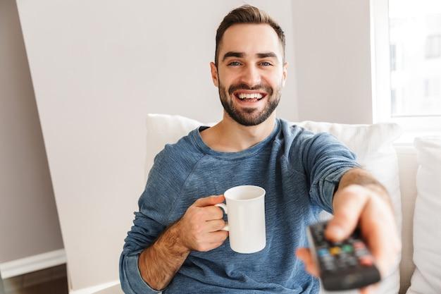 Sorridente giovane uomo seduto su un divano a casa, tenendo il telecomando della tv, bevendo caffè