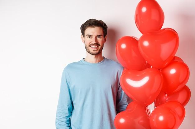 Il giovane sorridente in piedi con i palloncini del cuore e che sembra felice, celebra il giorno di san valentino, porta un regalo romantico all'amante, in piedi su sfondo bianco.