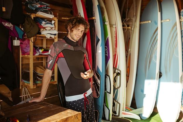 Sorridente giovane uomo in costume da bagno utilizza lo smartphone mentre levandosi in piedi nella capanna di surf