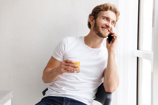Sorridente giovane uomo parla al telefono cellulare, guardando la finestra a casa, bevendo succo d'arancia
