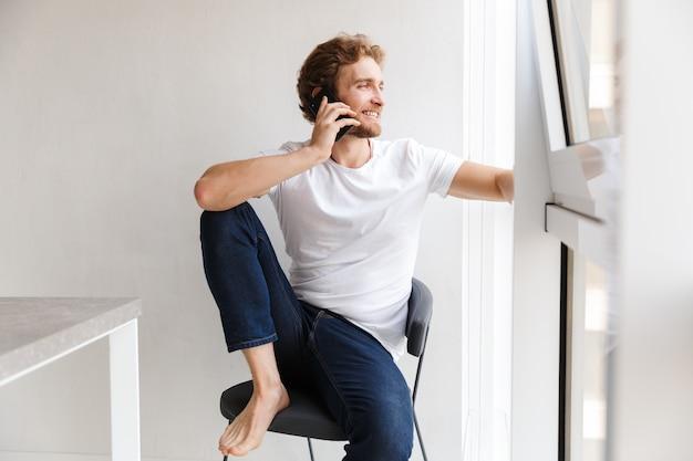 Giovane sorridente che parla sul telefono cellulare, guardando la finestra a casa