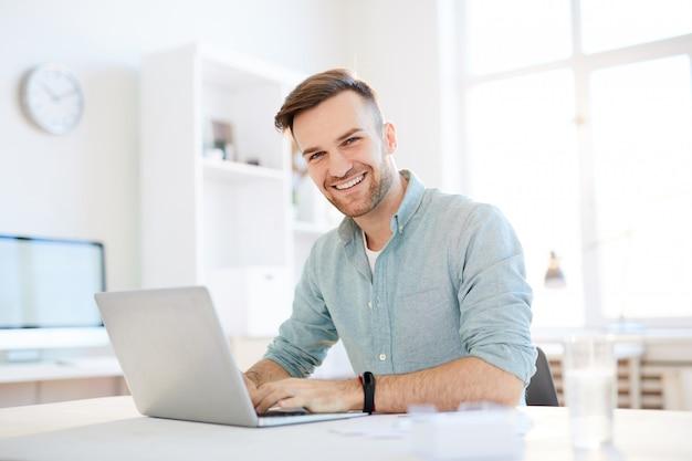Giovane sorridente che per mezzo del computer portatile