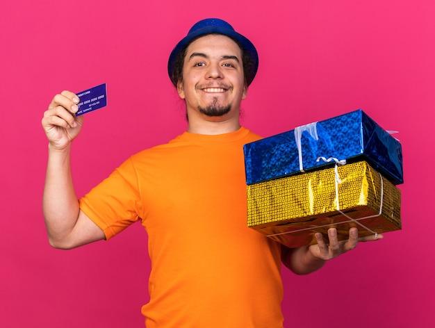 Sorridente giovane uomo che indossa cappello da festa in possesso di scatole regalo con carta di credito isolata sulla parete rosa