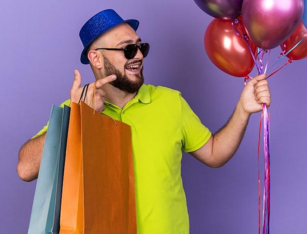 Sorridente giovane uomo che indossa un cappello da festa con occhiali che tengono palloncini con un sacchetto regalo punti a lato