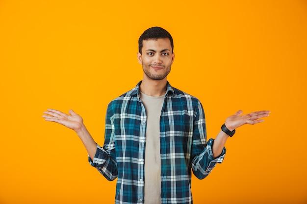 Sorridente giovane uomo che indossa la camicia a quadri in piedi isolato sopra la parete arancione, mostrando lo spazio della copia