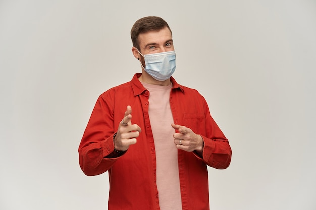 Giovane sorridente con la barba in camicia rossa e maschera igienica per prevenire l'infezione in piedi e puntando su di te verso la telecamera con due dita sul muro bianco