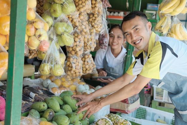 Venditori sorridenti della donna e del giovane che visualizzano l'assortimento del deposito della frutta
