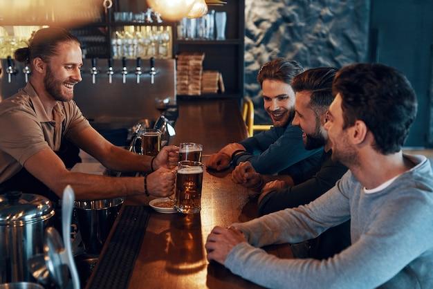 Giovani sorridenti in abiti casual che bevono birra e si uniscono mentre sono seduti al pub