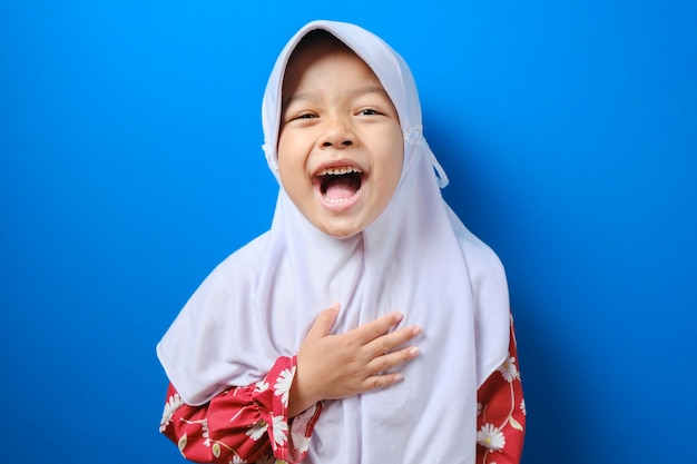 Sorridente giovane ragazza musulmana in abiti rossi hijab, guardando la telecamera isolata su sfondo blu muro, ritratto in studio. concetto di stile di vita religioso della gente.