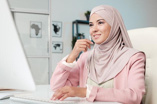 Sorridente giovane manager musulmano in hijab rosa che utilizza auricolari mentre comunica tramite un'app di videoconferenza sul computer in ufficio