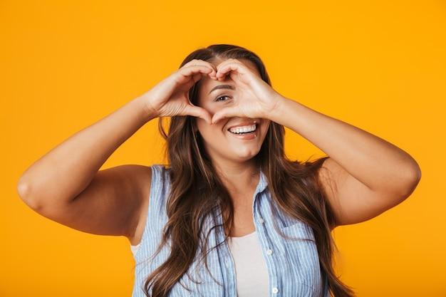 Sorridente giovane donna sovrappeso, mostrando il gesto del cuore