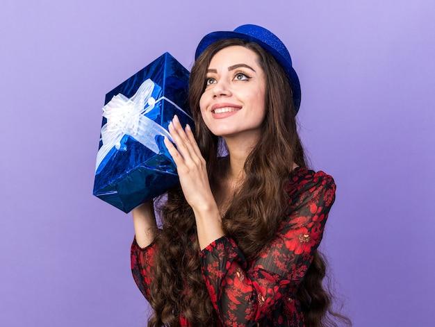 Sorridente ragazza di partito che indossa cappello da festa tenendo il pacchetto regalo vicino alla testa guardando in alto isolato sul muro viola