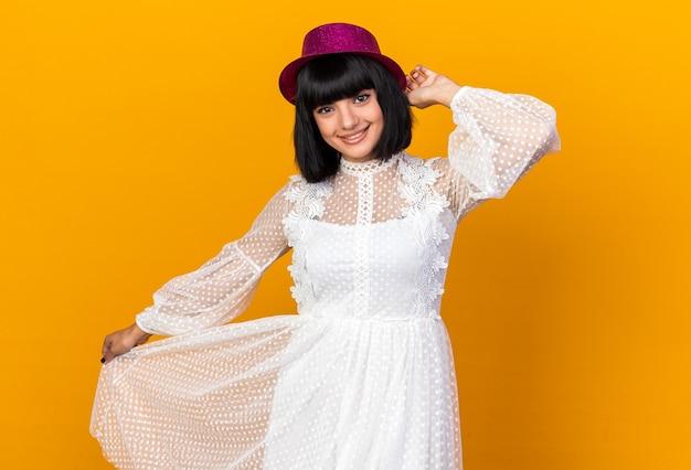 Sorridente ragazza festaiola che indossa cappello da festa alzando la mano afferrando e tirando a lato il suo vestito isolato sul muro arancione
