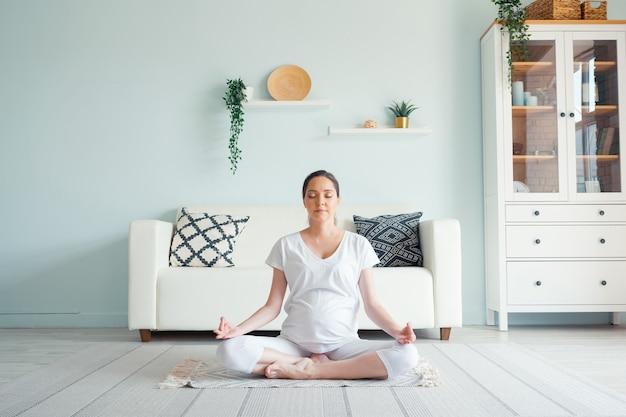 Sorridente giovane donna incinta in bianco medita seduto in posizione yoga padmasana sul pavimento contro mobili di design in una spaziosa stanza a casa