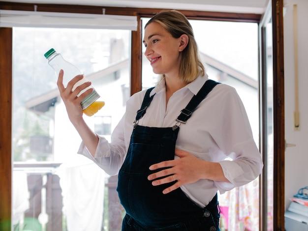 Sorridente giovane donna incinta in piedi e guardando una lattina di succo.