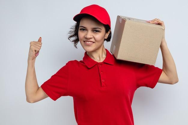 Sorridente giovane bella donna di consegna tenendo la scatola di cartone sulla spalla e tendendo i suoi bicipiti