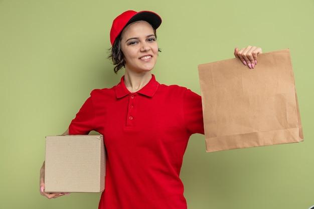 Sorridente giovane graziosa donna delle consegne che tiene in mano un imballaggio alimentare di carta e una scatola di cartone