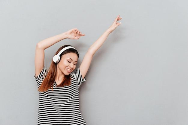 Musica d'ascolto sorridente della giovane donna graziosa con le cuffie