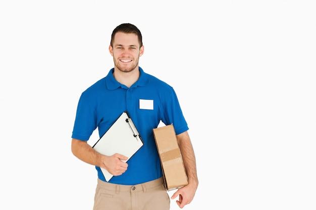 Sorridente giovane venditore con pacco e appunti