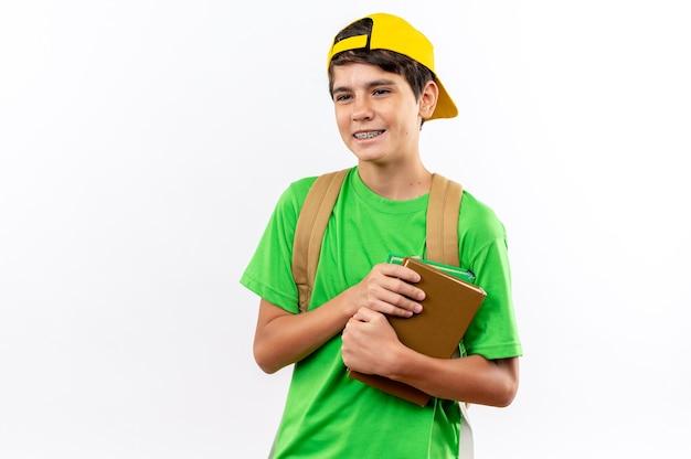 Sorridente giovane scolaro che indossa uno zaino con berretto che tiene libri