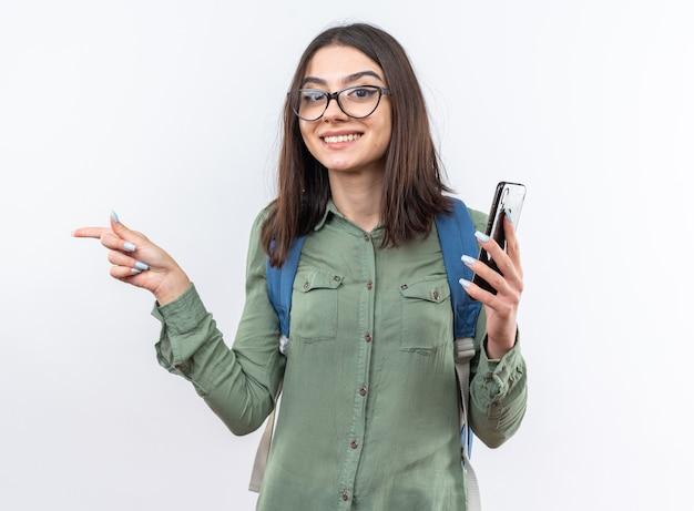 Sorridente giovane scuola donna con gli occhiali con zaino tenendo i punti del telefono a lato