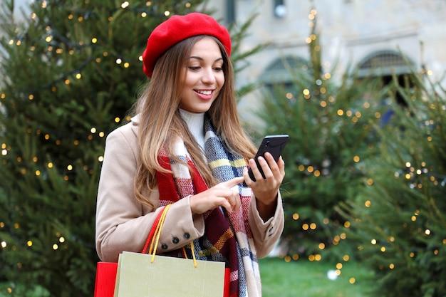 Sorridente giovane donna shopper acquisto online su smartphone in una strada cittadina con alberi di natale