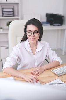 Sorridente giovane donna intelligente con gli occhiali seduto alla scrivania e utilizzando il computer moderno in ufficio