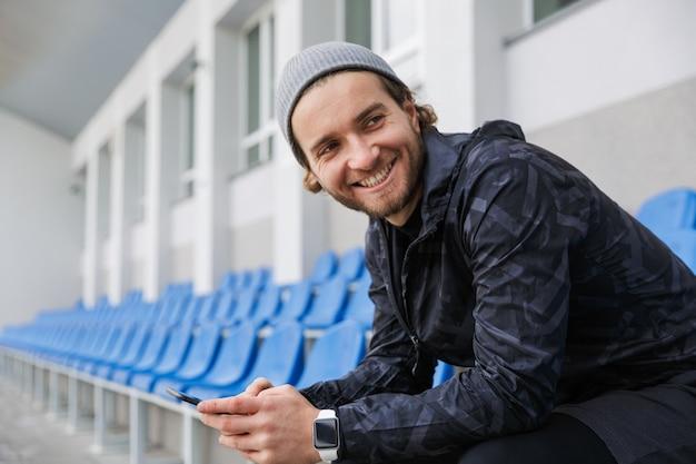 Sorridente giovane sportivo seduto sui sedili della tribuna allo stadio, utilizzando il telefono cellulare