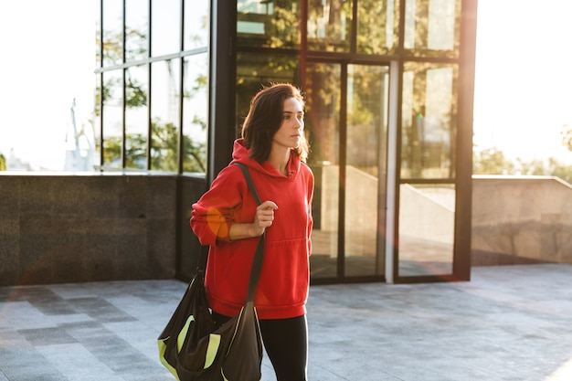 Sorridente giovane sportiva che indossa una felpa con cappuccio camminare all'aperto, portando la borsa sportiva