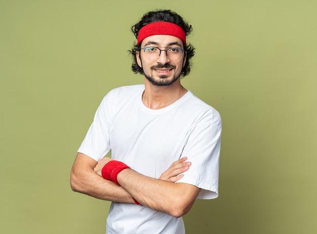 Sorridente giovane sportivo che indossa fascia con cinturino incrociando le mani