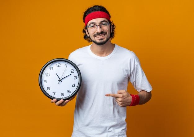 Sorridente giovane sportivo che indossa la fascia con il braccialetto che tiene e punta all'orologio da parete