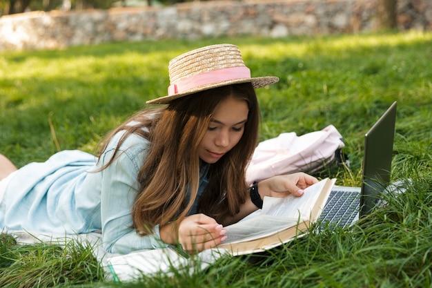Sorridente giovane ragazza adolescente posa su un prato al parco