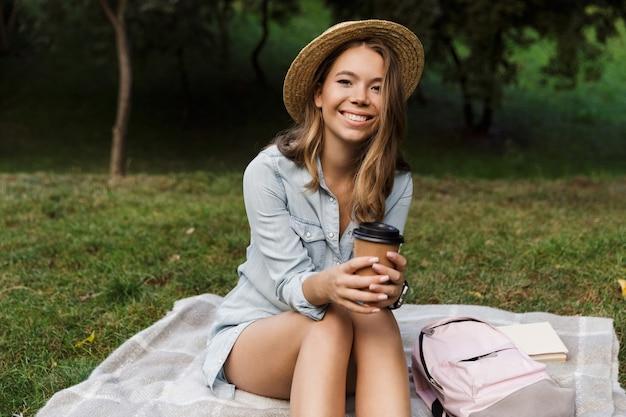Sorridente giovane ragazza adolescente con zaino seduto